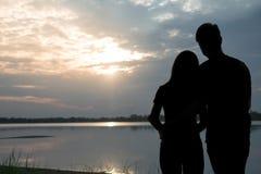 Konturn av ett romantiskt paranseende som kramar sig och håller ögonen på solnedgången Romansk och förälskelsebegrepp arkivbild