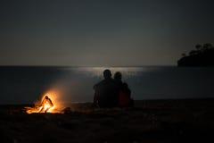 Konturn av ett ungt par på sommar sätter på land nära lägereld på mo Arkivfoton