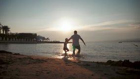 Konturn av fadern och hans lilla dotter k?r lyckligt in i havet p? solnedg?ngen F?rgst?nk flyger in i deras arkivfilmer