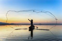Konturn av fiskaren som trowing, förtjänar under solnedgång Royaltyfria Bilder