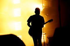 Konturn av gitarrspelaren, gitarrist utför på konsertetapp Royaltyfri Foto