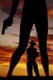 Konturn av kvinnaben med vapnet rymmer ner cowboyen Royaltyfria Bilder
