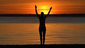 Konturn av kvinnan med armar lyftte att stå på havhavsstranden som ser på vågor på solnedgången Praktisera kondition för flicka arkivfilmer