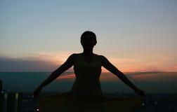 Konturn av kvinnan som sträcker armar, tycker om kopplar av på solnedgången Arkivfoton