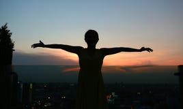 Konturn av kvinnan som sträcker armar, tycker om kopplar av på solnedgången Royaltyfri Foto