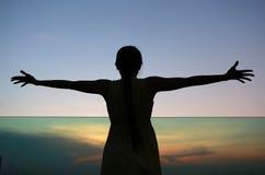 Konturn av kvinnan som sträcker armar, tycker om kopplar av på solnedgången Royaltyfria Bilder