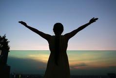 Konturn av kvinnan som sträcker armar, tycker om kopplar av på solnedgången Arkivfoto