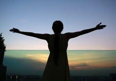 Konturn av kvinnan som sträcker armar, tycker om kopplar av på solnedgången Arkivbild