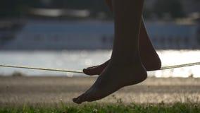 Konturn av kvinnlign lägger benen på ryggen på ett slacklinerep lager videofilmer