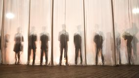 Konturn av männen bak gardinen i teatern på etapp, skuggan bak platserna är liknande till viten och blaen Arkivfoto