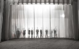 Konturn av männen bak gardinen i teatern på etapp, skuggan bak platserna är liknande till viten och blaen Arkivfoton