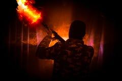 Konturn av mannen med anfallgeväret som var klart att anfalla på mörker, tonade dimmig bakgrund eller den farliga banditen i svar Arkivfoton