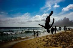 Konturn av mannen som perfoming en baksida, slår en kullerbytta i pikposition på den Ipanema stranden, Rio de Janeiro, Brasilien royaltyfri bild