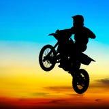 Konturn av motocrossryttaren hoppar i himlen Arkivbild