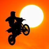 Konturn av motocrossryttaren hoppar i himlen Arkivfoto