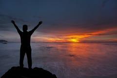 Konturn av pojken med händer lyftte till den härliga solnedgången Royaltyfri Fotografi