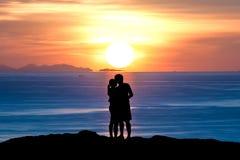 Konturn av romantiker ett par kramar att kyssa mot en solnedgånghimmel Royaltyfri Foto
