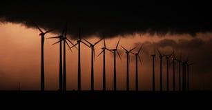 Konturn av roterande vindturbiner är bakbelyst vid exponeringar av blixt från en storm royaltyfri bild
