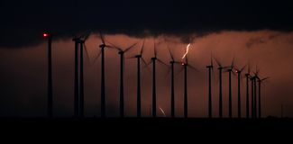 Konturn av roterande vindturbiner ?r bakbelyst vid exponeringar av blixt fr?n en storm royaltyfri fotografi