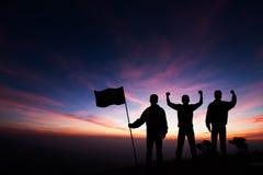 Konturn av tre unga män som står överst av berget med nävar, lyftte upp och rymma flaggan på soluppgångbakgrund royaltyfri fotografi