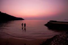 Konturn av vännen på stranden, solnedgång, skymning royaltyfri foto
