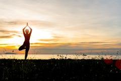 Konturn för kvinnan för meditationyogalivsstilen på havssolnedgången, kopplar av livsviktigt arkivfoton