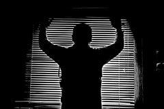 Konturn i monokrom av en man i ett fönster rev av modellmörker fotografering för bildbyråer