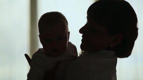 Konturn som älskar modern som spelar med henne, behandla som ett barn i bakgrunden av ett fönster arkivfilmer