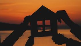 Konturn som ett litet pappers- hus gjorde av papp, rymms med händer mot på havssolnedgång Effektivitet och hem- begrepp - lager videofilmer