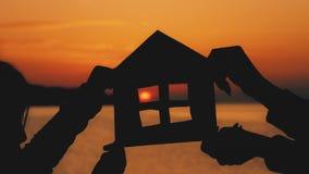 Konturn som ett litet pappers- hus gjorde av papp, rymms med händer mot på havssolnedgång Effektivitet och hem- begrepp - stock video