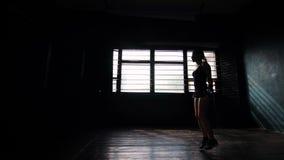 Konturn som panorerar den unga målmedvetna kvinnliga boxaren, i slåget in, förbinder händer som hoppar på överhopprep stock video