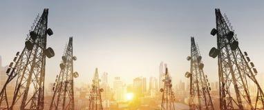 Konturn telekommunikation står högt med TVantenner och den satellit- maträtten i solnedgång, med staden för dubbel exponering i s Arkivbild
