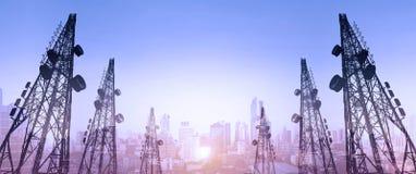 Konturn telekommunikation står högt med TVantenner och den satellit- maträtten i solnedgång, med staden för dubbel exponering i s Arkivfoton