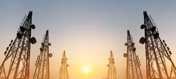 Konturn telekommunikation står högt med TVantenner och den satellit- maträtten i solnedgången, panoramasammansättning Royaltyfria Bilder