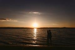 Konturpar i havet på solnedgången arkivbild