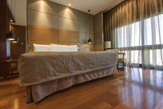Konung-storleksanpassa sängen med nattduksbordet och lampor Arkivbild