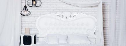 Konungformatsäng i vindlägenhet Vindstilsovrum med den vita designen royaltyfria foton
