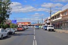 Konungvägen till och med den Tavua staden, Fiji med återförsäljnings- shoppar och medel som parkeras på vägrenen Arkivfoto
