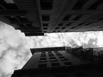 Konvergerande byggnader till himlen arkivbild
