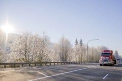 Konvoi von den roten halb LKWs der großen Anlagen, die mit Fracht auf Winterlandstraße mit eisigen Bäumen des Schnees laufen lizenzfreie stockfotografie