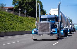 Konvoi von großen der Anlagen LKWs halb auf der Straße mit blauem klassischem Ame Lizenzfreie Stockbilder
