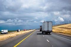 Konvooi van grote installaties semi vrachtwagens met aanhangwagens in beide richtingen stock afbeeldingen
