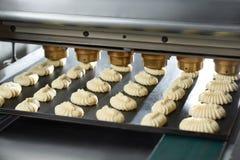 Konwejer linia robi małym tortom od surowego ciasta Fotografia Stock