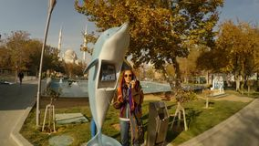 Girl calls in the phone booth in the form of a dolphin in the center of Konya. KONYA / TURKEY - 11.20.2016 central streets of the ancient Turkish city stock footage