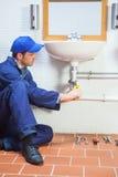 Konzentration des Klempners, der Wanne repariert Stockbilder