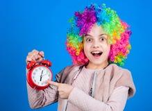Konzentrieren auf Genauigkeit Glückliches kleines Kind, das auf Wecker zeigt Wenig Mädchen, das mit Uhr lächelt Genauigkeit und N stockfotografie