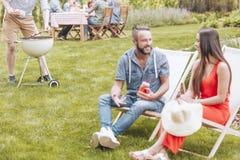 Konzentrieren Sie sich auf die shashliks, die auf einen Grill gesetzt werden Ein Paar junge Leute stockbild