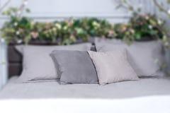 Konzentrieren Sie sich auf graue Kissen, gemütliches Bett mit Blumen auf dem Bettgestell und Lizenzfreies Stockbild