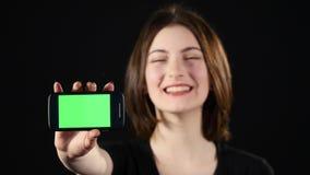 Konzentrieren Sie sich auf Handy Junge Frau übergibt den leeren Smartphoneschirm an zeigen, der auf grünem Hintergrund lokalisier Stockbild