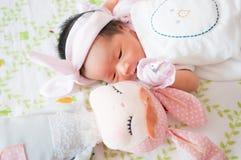 Konzentrieren Sie sich am Baby mit nettem Stirnband beim Dösen und Spielen mit netter Puppe auf das Bett Neugeborenes Mädchen ist Lizenzfreie Stockfotografie
